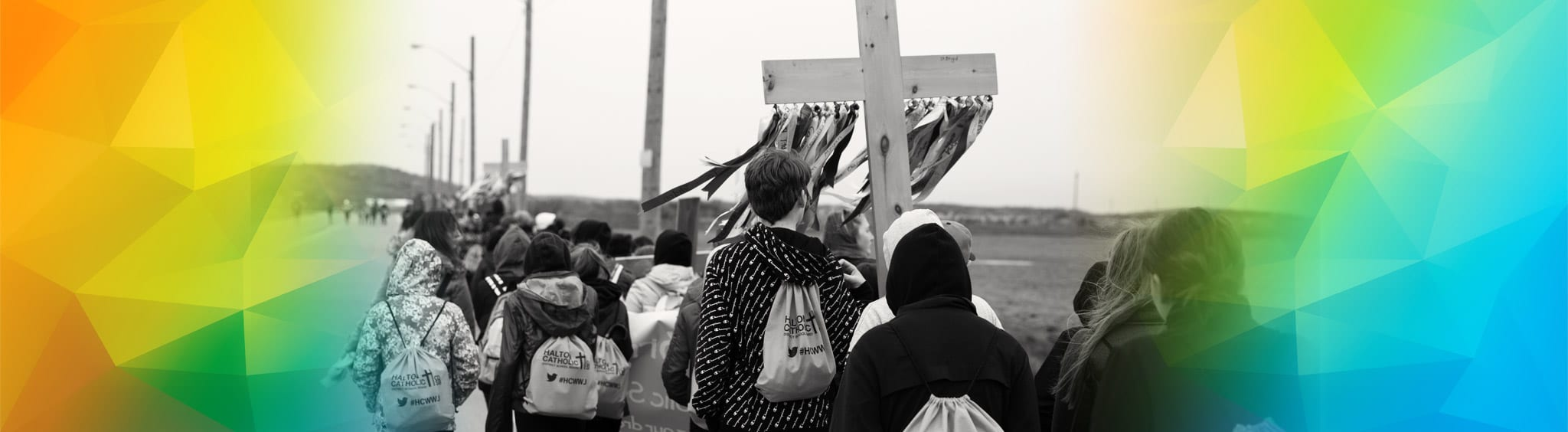 Students walking together carrying cross as part of Walk With Jesus event
